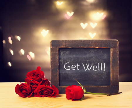 well: Get well message on a small chalkboard with red roses