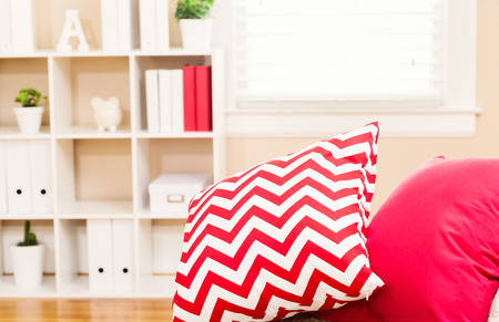 red sofa: Bright living room interior with red sofa pillows
