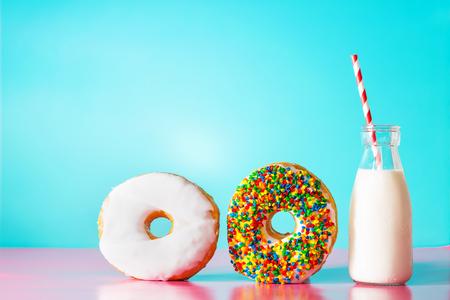 leuchtend: Donuts mit Milch auf einem Pastell blau und rosa Hintergrund