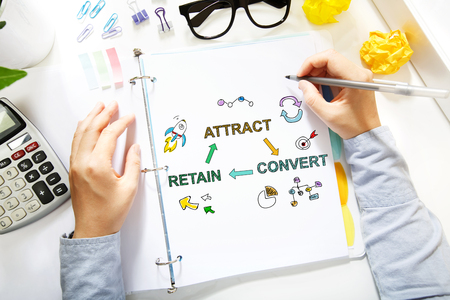 white person: Person drawing Attract, Convert and Retain concept on white paper in the office
