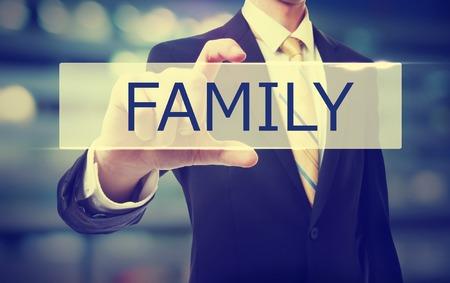 hombre de negocios que sostiene la familia en el fondo borrosa resumen