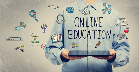 Online Education concept with young man holding a tablet computer Stock Photo