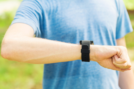 Male jogger outside looking at his smart watch