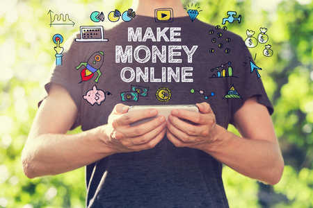 money online: Make Money Online  concept with young man holding his smartphone outside in the park toward sunset