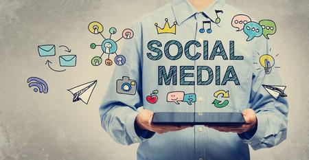 medios de comunicacion: del concepto de medios sociales con el hombre joven sosteniendo un tablet PC