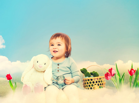 baby toys: Toddler girl with white bunny in spring day