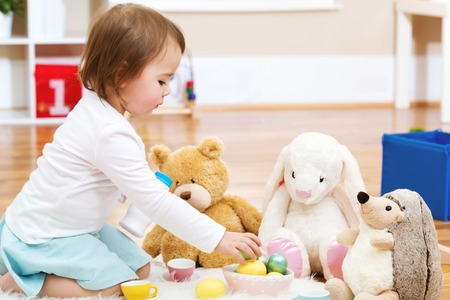 stuffed animals: Toddler girl playing with her stuffed animals in her house Stock Photo