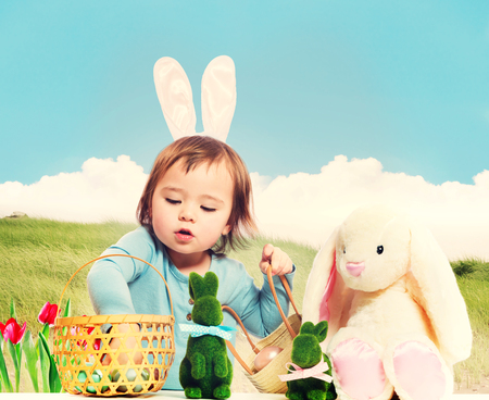 stuffed animals: Toddler girl collecting Easter eggs with bunny companions Stock Photo