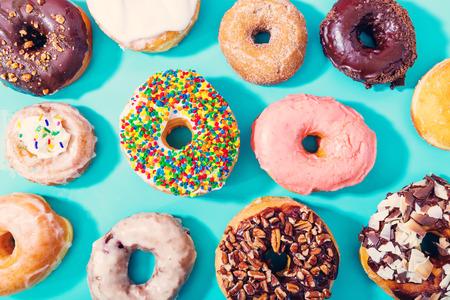 パステル ブルーの背景に各種ドーナツ