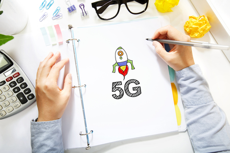 5g: Person drawing 5G concept on white paper in the office