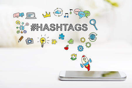 post: Hashtags concept with smartphone on white table Stock Photo