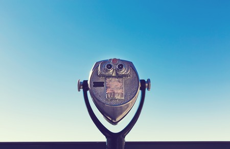 Coin-operated binoculars against the blue sky