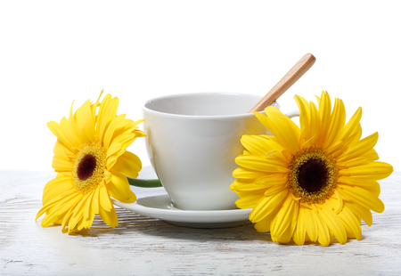 Coffee cup with yellow gerberas on white background