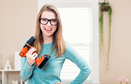 Young woman with cordless drill ready for home repairs