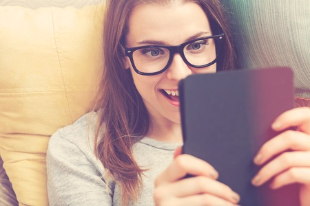 e book device: Happy young woman reading an e-book on her couch at home Stock Photo