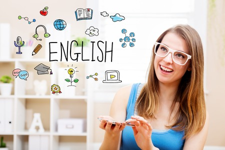 woman smartphone: English concept with young woman wearing white glasses using her smartphone in her home Stock Photo