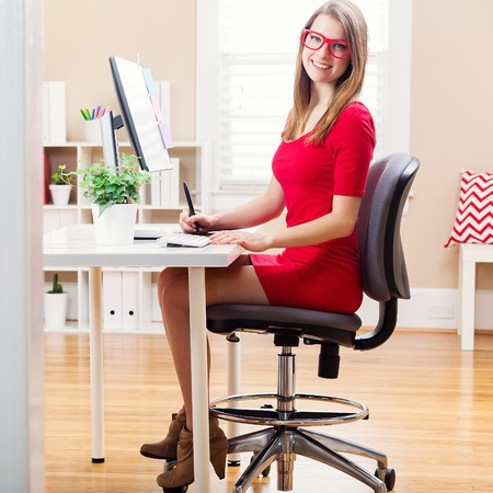 working desk: Happy young woman working with a pen stylus tablet in her home office