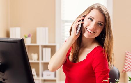 행복한 젊은 여자가 그녀의 홈 오피스 전화로 말하기