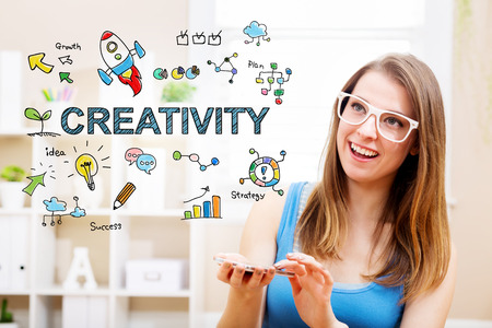Creativity concept with young woman wearing white glasses using her smartphone in her home