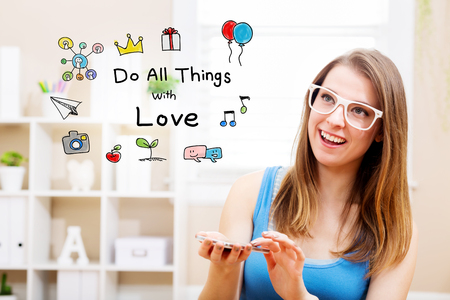 Do all things with love concept with young woman wearing white glasses using her smartphone in her home