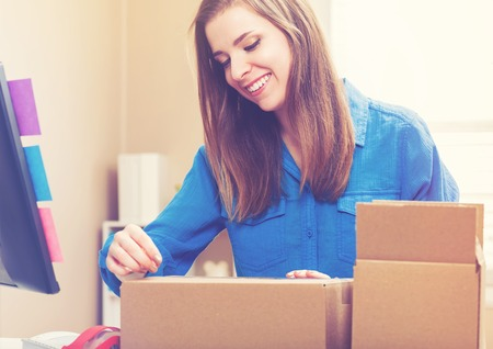 shipped: Young woman taping boxes to be shipped in her home office