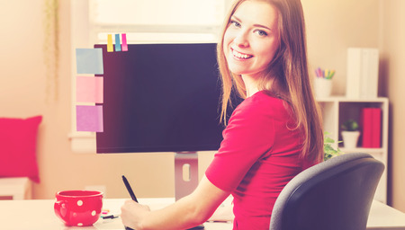 stylus: Happy young woman working with a pen stylus tablet in her home office