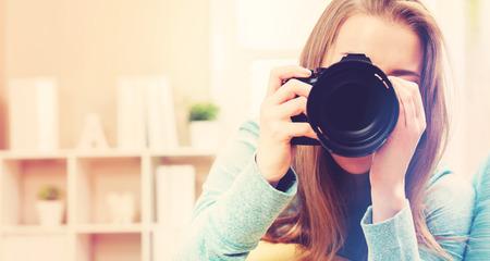 デジタル一眼レフ カメラを持つ若い女性カメラマン 写真素材