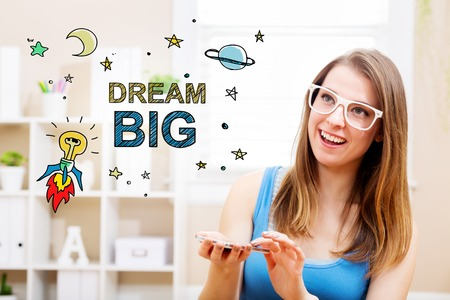 woman smartphone: Dream big concept with young woman wearing white glasses using her smartphone in her home