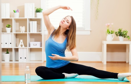 woman stretching: Happy young woman stretching in a her home studio