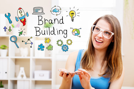 woman smartphone: Brand building concept with young woman wearing white glasses using her smartphone in her home