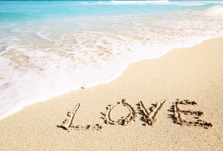 inscribed: Love inscribed in the sand of a tropical beach