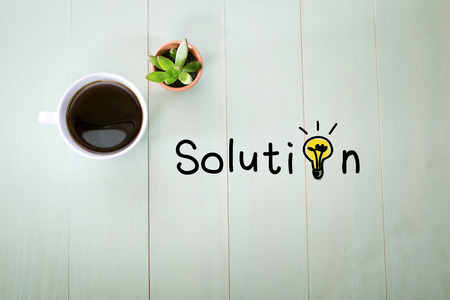 Solution concept with a cup of coffee on a pastel green wooden table