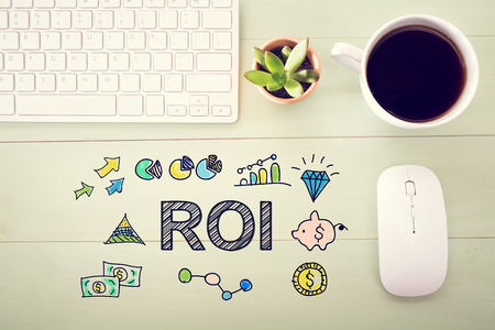 workstation: ROI concept with workstation on a light green wooden desk Stock Photo