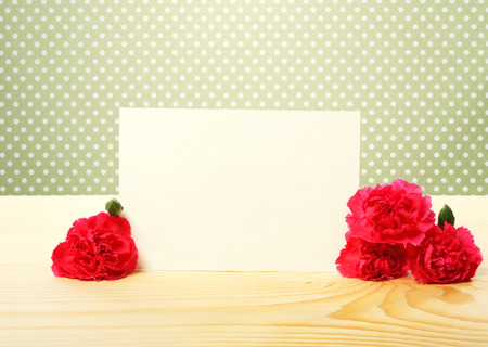 Blank Off White Greeting Card with Attractive Carnation Flowers on Top of a Wooden Table with Green Polka Dots Background Stock Photo