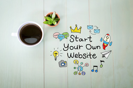 desk top: Start Your Own Website concept with a cup of coffee on a pastel green wooden table
