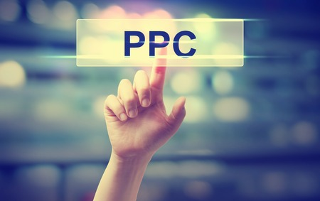 click button: PPC - Pay Per Click concept with hand pressing a button on blurred abstract background Stock Photo