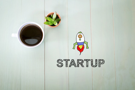 Startup concept with a cup of coffee on a pastel green wooden table