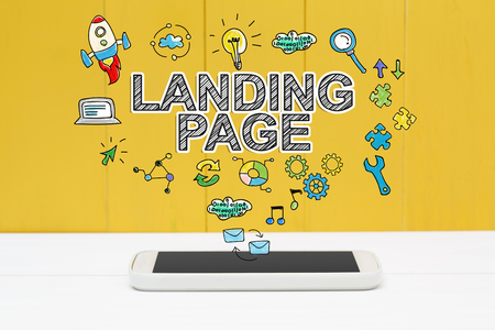 Landing Page concept with smartphone on yellow wooden background Фото со стока