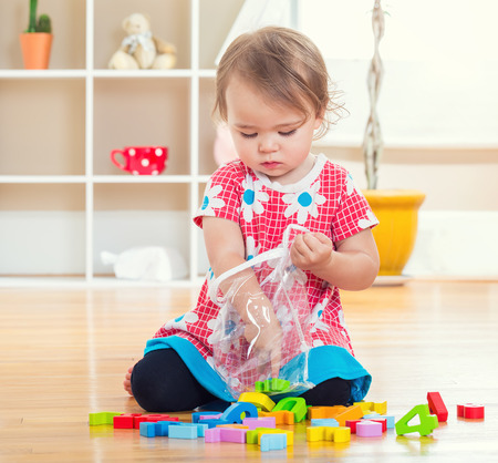 baby toys: Toddler girl playing with her toys inside her house
