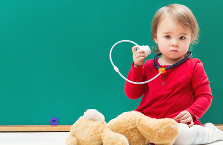 school nurse: Happy toddler girl caring for her teddy bear with a stethoscope