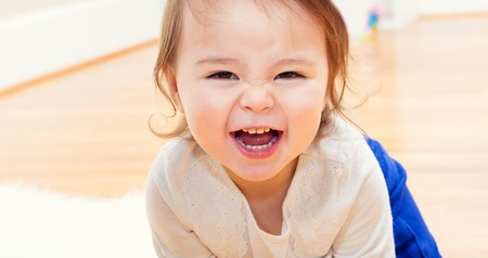baby playing: Happy toddler girl with a giant smile in her house Stock Photo