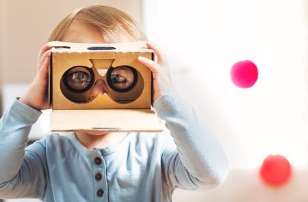 Dziewczyna maluch przy użyciu nowego zestawu słuchawkowego wirtualnej rzeczywistości Zdjęcie Seryjne