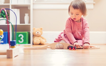 play room: Happy toddler girl playing with toys in her house