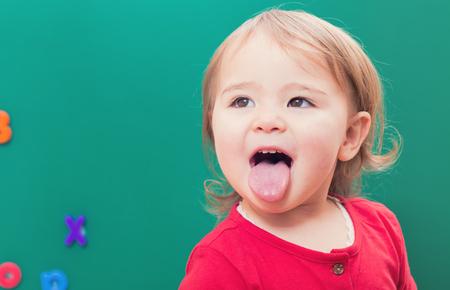 lengua afuera: Muchacha feliz del niño que se pega la lengua hacia fuera delante de una pizarra verde