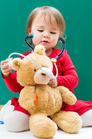 niños jugando en la escuela: Muchacha feliz del niño que cuida para su oso de peluche con un estetoscopio