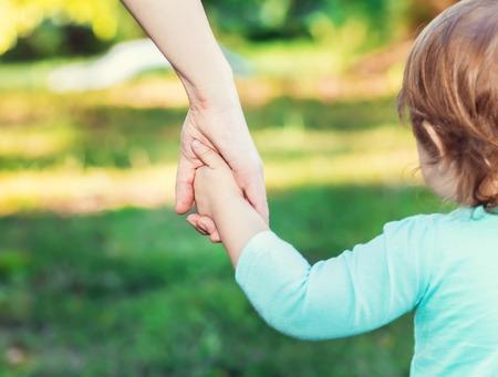 manos entrelazadas: Muchacha del ni�o de la mano con su madre fuera Foto de archivo