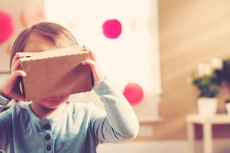 Muchacha del niño utilizando un nuevo casco de realidad virtual Foto de archivo