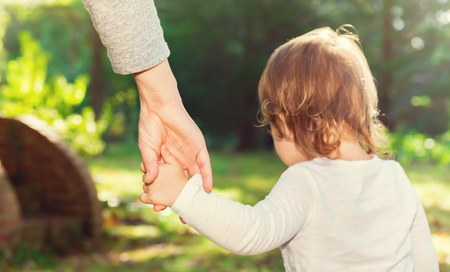 adult hand: Toddler girl holding her parents hand while walking outside Stock Photo