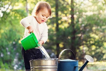 外の水まき缶で遊んで幸せな幼児の女の子 写真素材