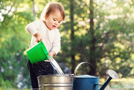 Happy toddler girl playing with watering cans outside 스톡 콘텐츠